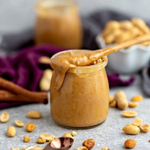 Side view of homemade peanut butter in a jar with a spoon