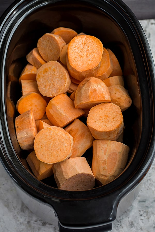 Top view of raw sweet potato rounds in a slow cooker