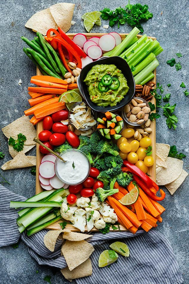 Top view of paleo veggie platter on a wooden tray on a grey background with Siete tortilla chips
