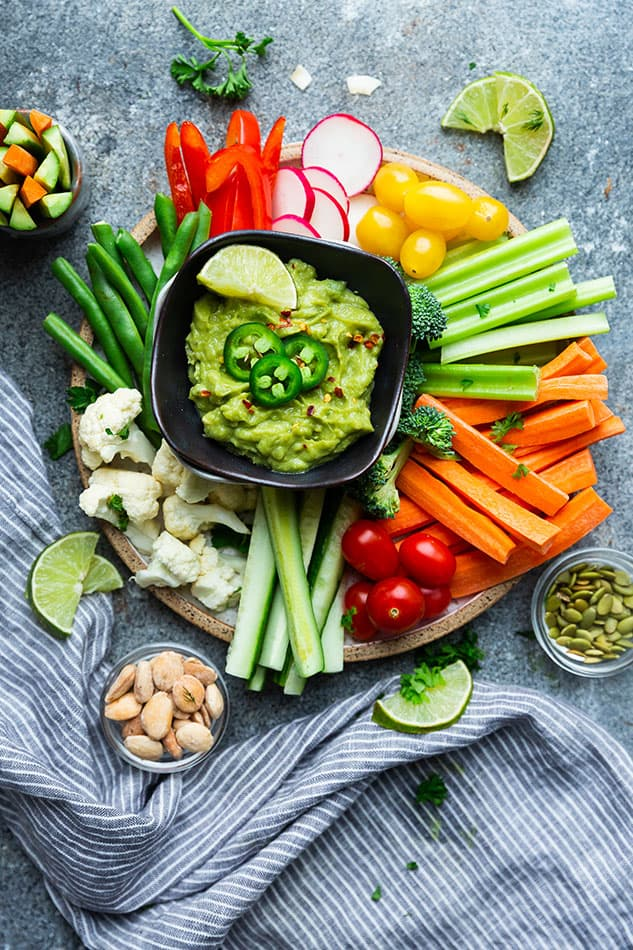 Overhead view of a veggie platter with bowls of guacamole and salsa