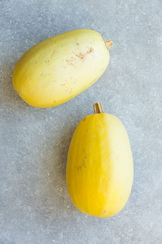 Two whole spaghetti squash on a gray background