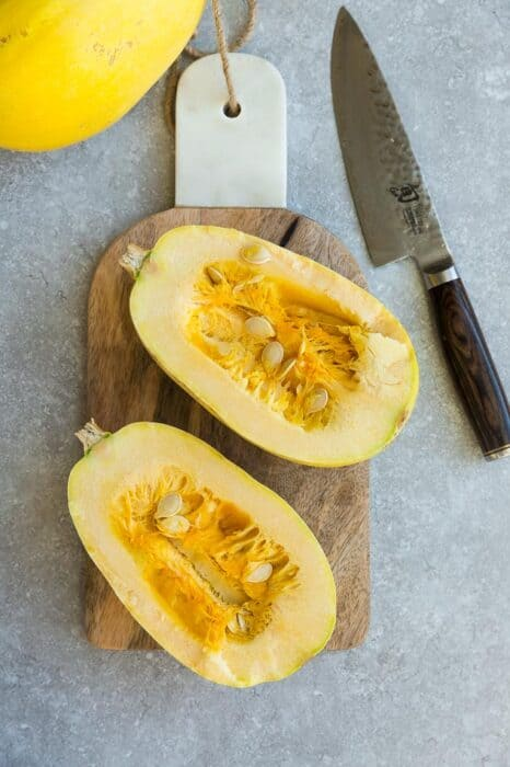 Overhead view of two raw spaghetti squash halves on a wooden cutting board