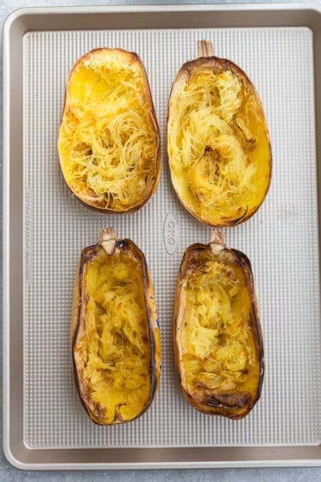 Overhead view of 4 roasted spaghetti squash halves on a baking sheet
