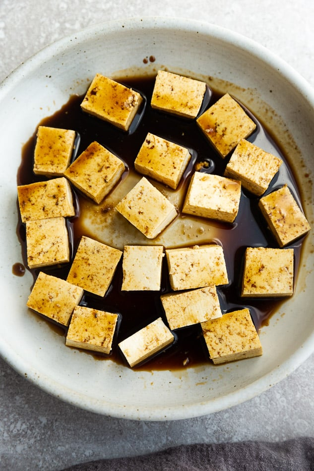 Top view of tofu blocks marinating in white bowl on grey surface.