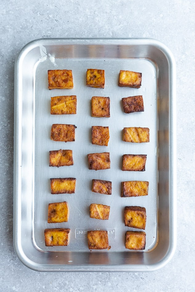 Top view of baked tofu cubes on a baking pan