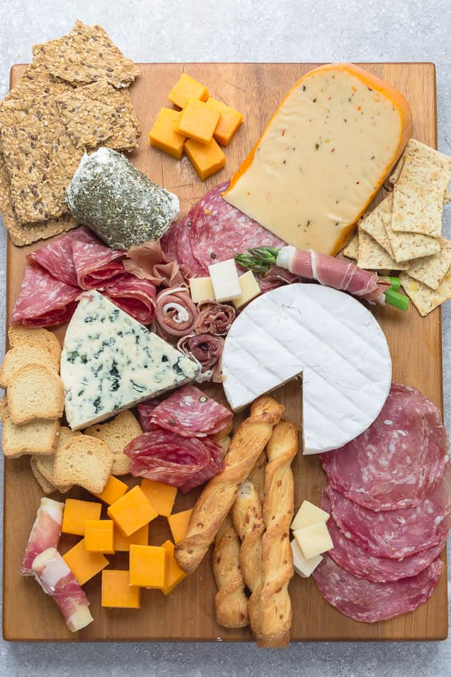 Top view of crackers, meats, and cheeses on a wooden board