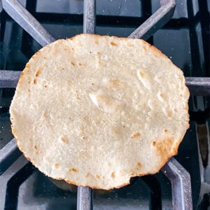 One tortilla shell over a gas burner