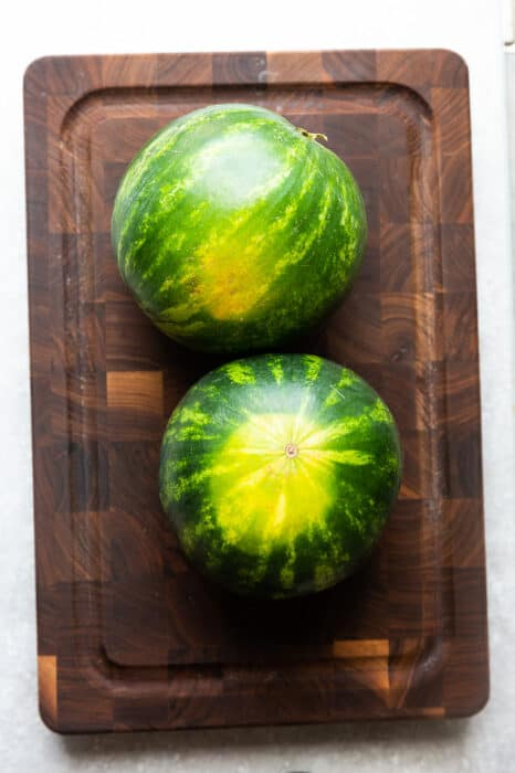 Top view of two mini watermelons on a wooden cutting board