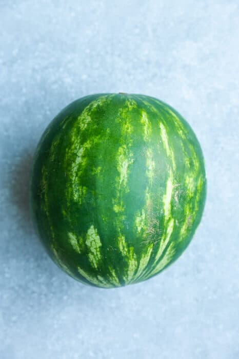 Top view of one medium watermelon on a grey surface