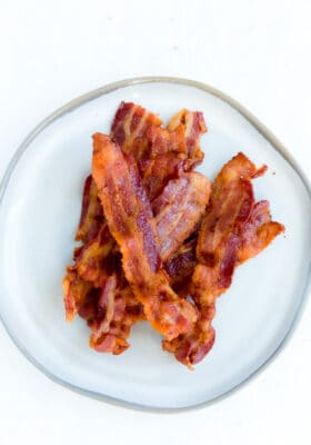 A Pile of Crispy Air Fryer Bacon on a White Plate with a Gray Rim