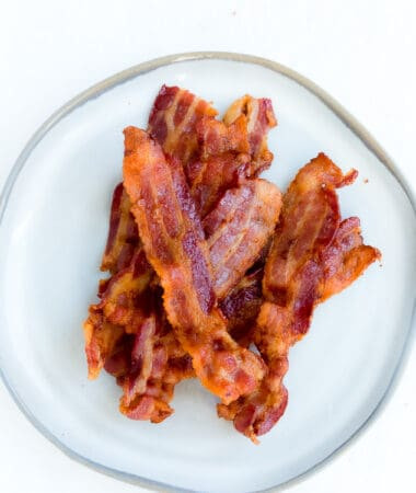 Top view of oven baked crispy bacon on a grey plate
