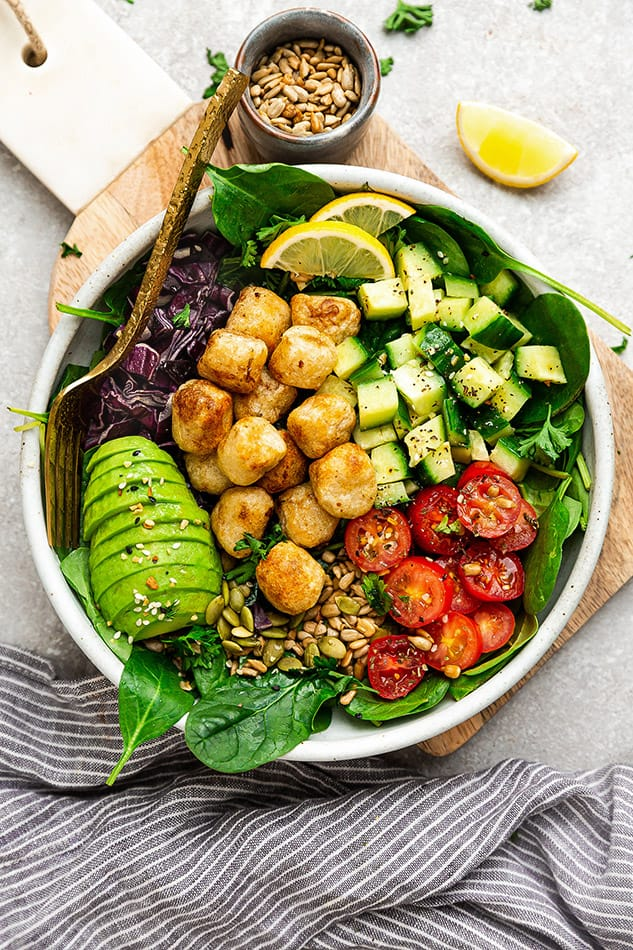 Top view of cauliflower gnocchi in a white bowl with spinach and avocado