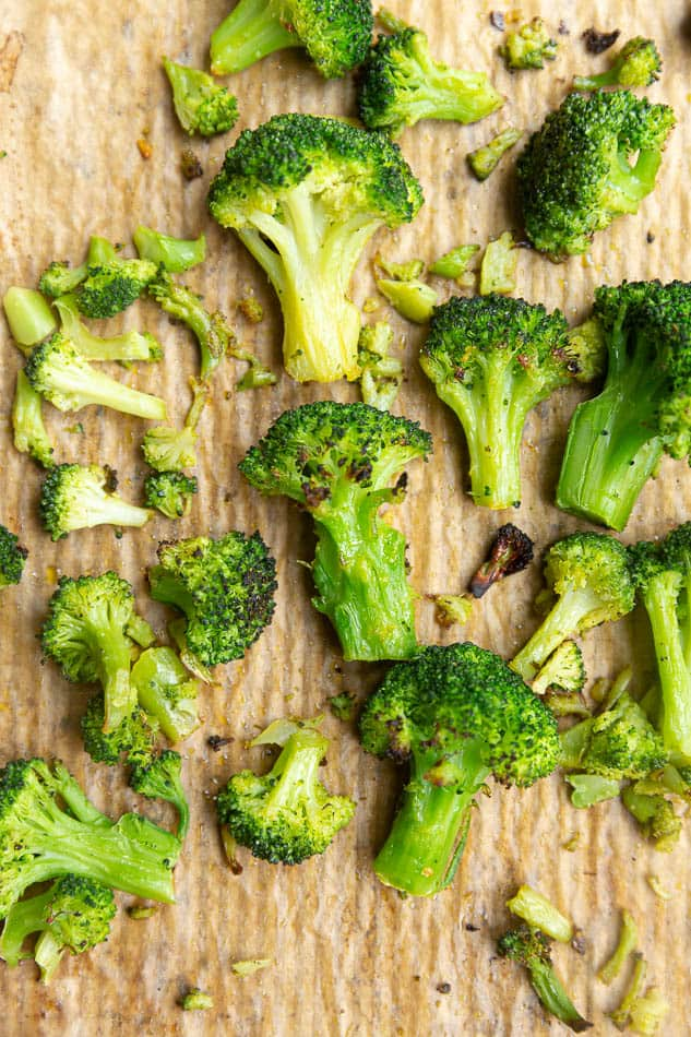 Overhead image of roasted broccoli on sheet with parchment paper.