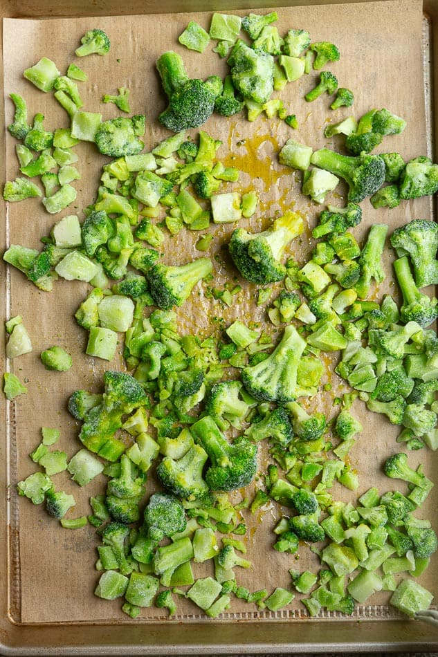 Frozen broccoli on tray sheet with oil.