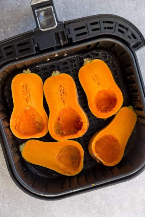 Top view of 5 honeynut squash halves in an air fryer basket