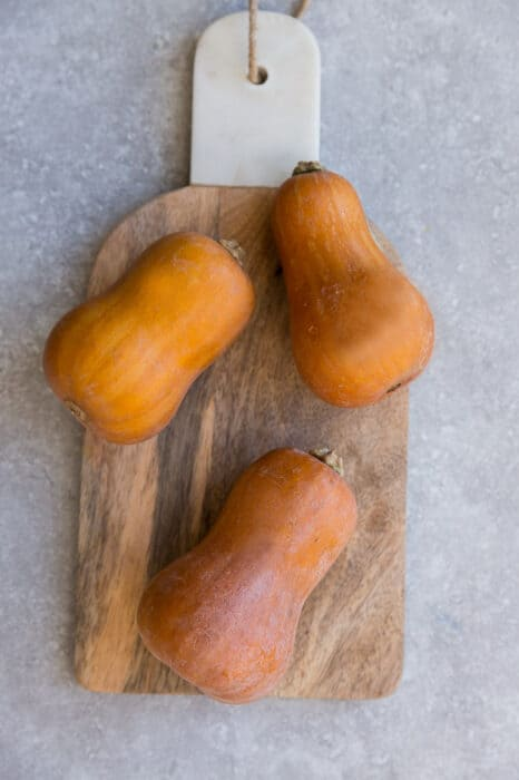 Top view of 3 whole honeynut squash on a wooden cutting on a grey background