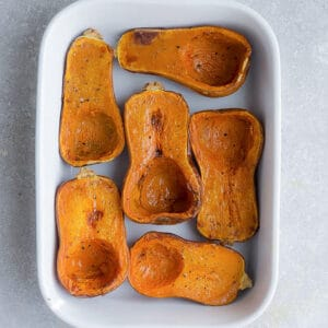 Top view of 6 honeynut squash halves in a white rectangle casserole dish