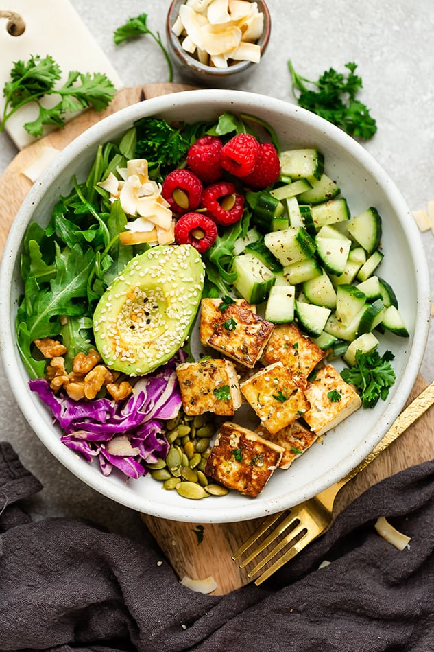 Colorful salad with tofu, avocado, cucumbers, and raspberries.
