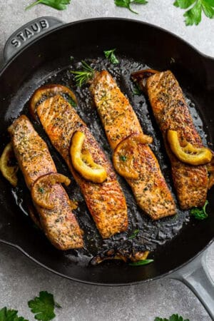 Top view of perfect pan fried salmon in a cast iron skillet with lemon slices