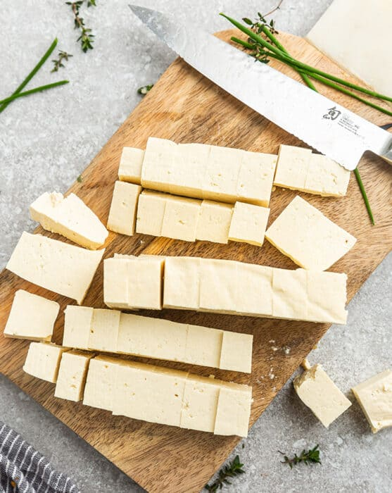 Top view of cut tofu cubes with a knife on a wooden cutting board