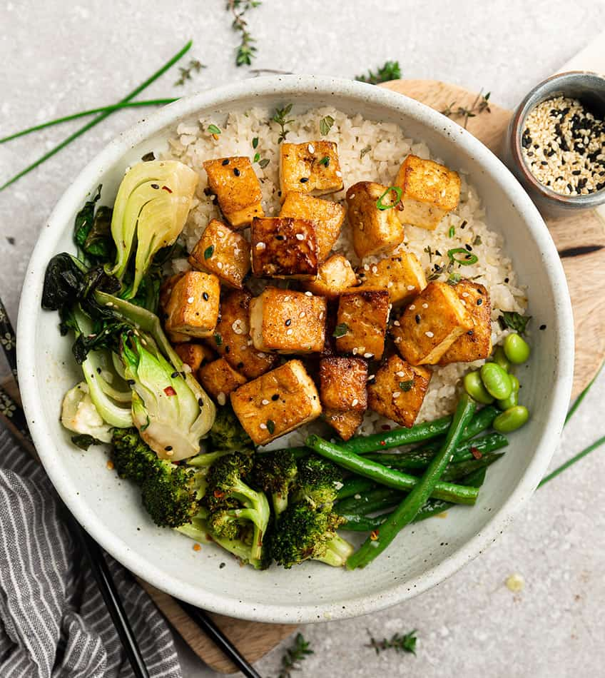 Top view of crispy air fryer tofu in a white bowl with cauilflower rice, broccoli, bok choy and green beans