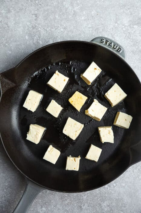 Top view of cubed uncooked tofu in a cast-iron pan on a grey background