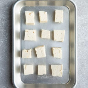 Top view of cubed uncooked tofu on a baking pan