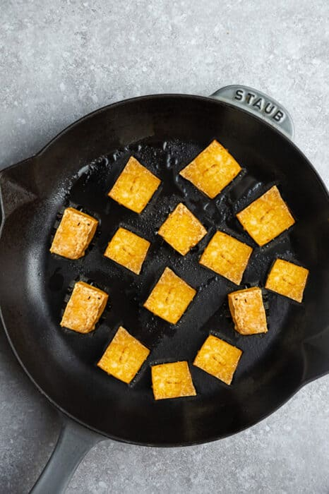 Top view of cubed crispy tofu in a cast-iron pan on a grey background