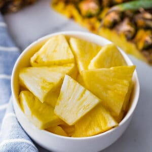 Top view of chopped pineapple cubes in a white bowl