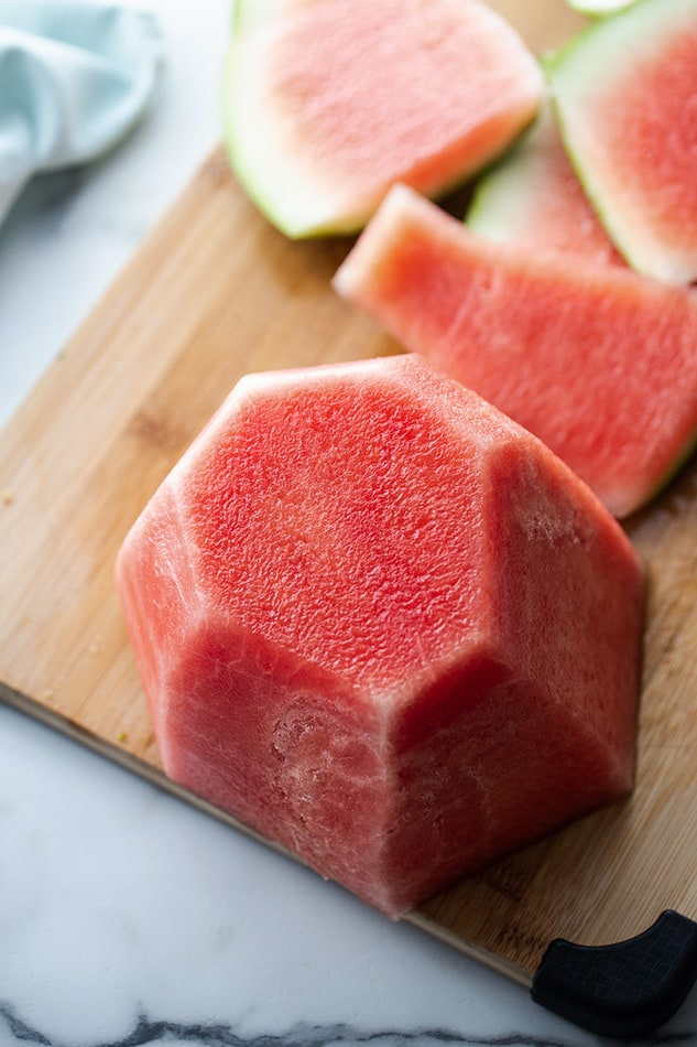 One view of cut watermelon on wooden cutting board.