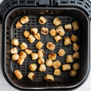 Top view of crispy air fried cauliflower gnocchi in an air fryer basket