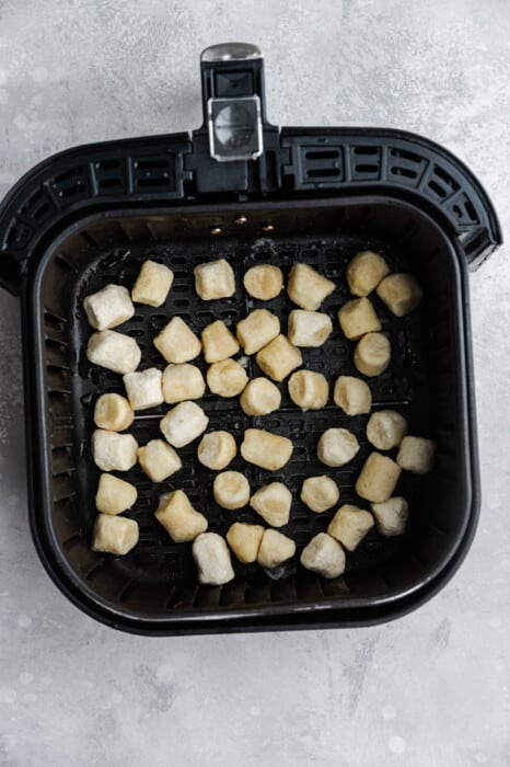 Top view of frozen cauliflower gnocchi in an air fryer basket