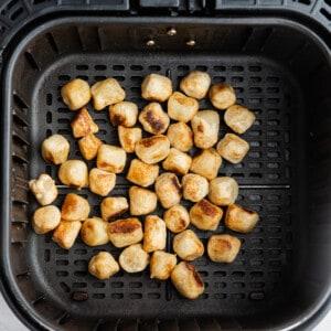 Top view of crispy air fried cauliflower gnocchi in an air fryer basket