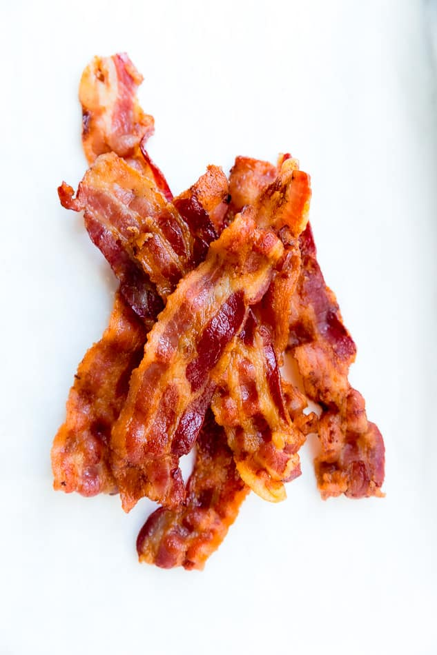 Top view of a pile of oven baked crispy bacon on parchment paper