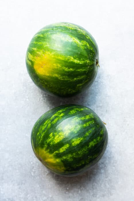 Top view of two mini watermelons on a grey surface