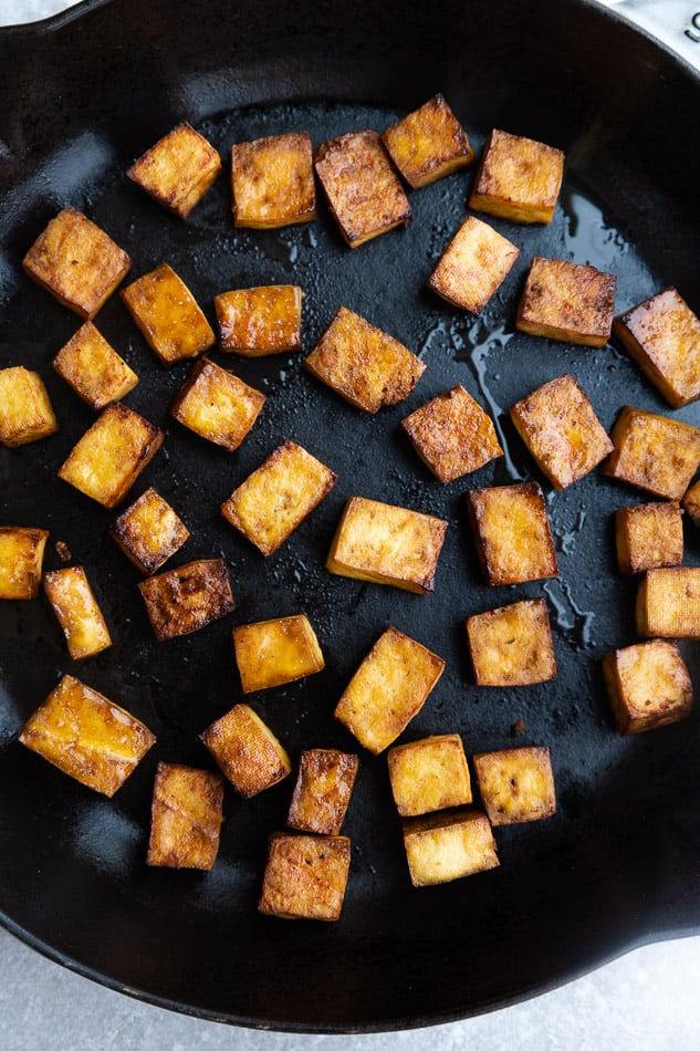 Top view of pan fried tofu on a cast iron skillet