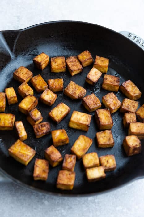 Side view of pan fried tofu on a cast iron skillet