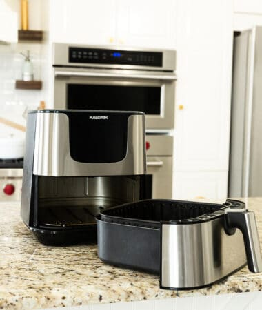 Front view of a silver air fryer on a counter with the basket opened