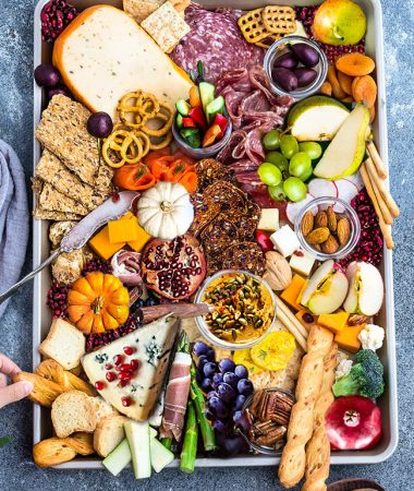 Top view of Fall Cheese Board with crackers, apples, pumpkins, pears, grapes, charcuterie etc.