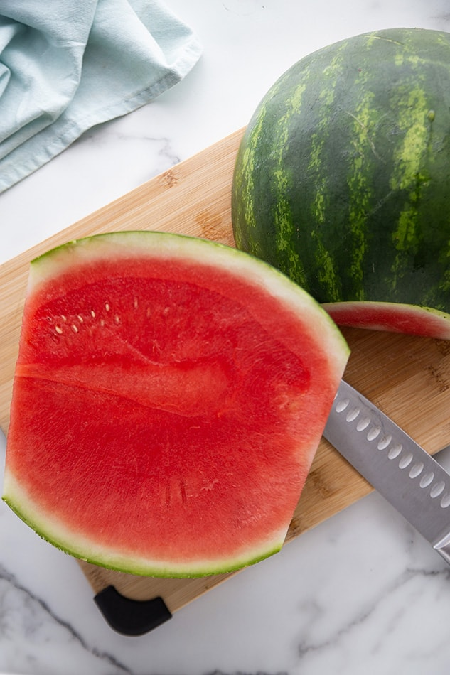One half of a watermelon sliced on wooden cutting board.