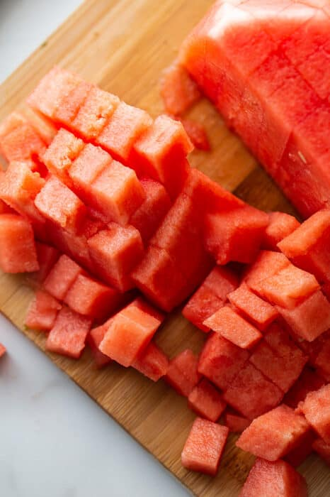 Top view of half of watermelon without the rind cut into cubes on a wooden cutting board