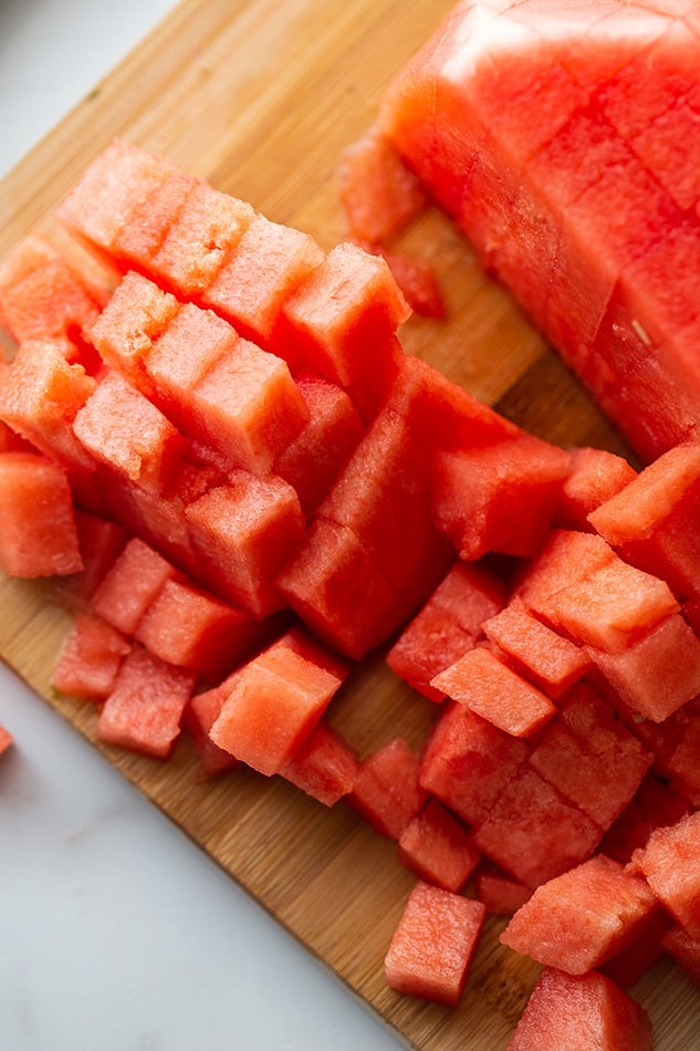 Watermelon cut into cubes on wooden cutting board.