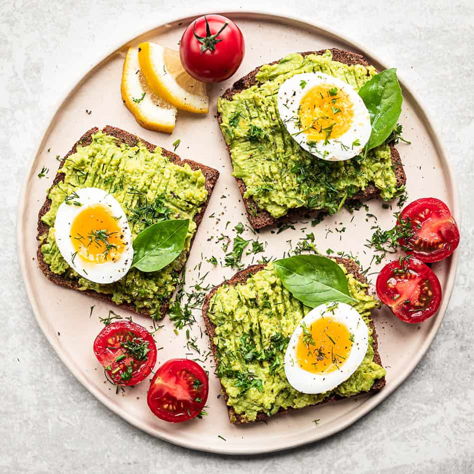 Three overhead images of avocado toast with eggs and tomatoes