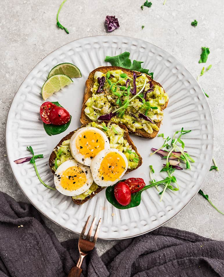 Overhead image of two avocado toast slices with eggs and micro greens.