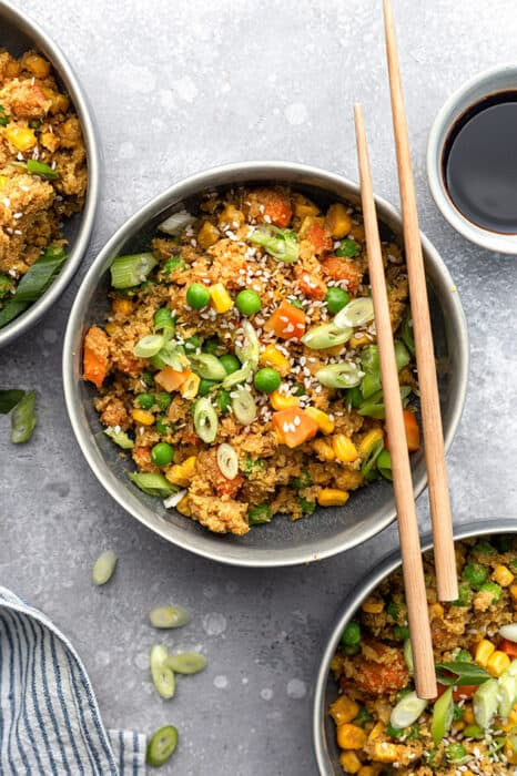 Top view of a bowl of easy cauliflower fried rice in a grey bowl with chopsticks