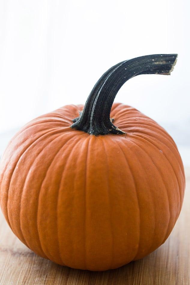A whole pie pumpkin on a wooden board