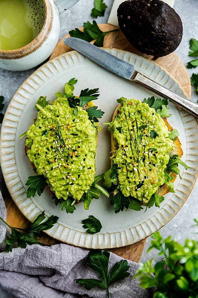 Overhead image of avocado toast with butter knife and matcha tea.