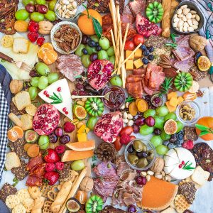 Top view of a holiday cheese board with a variety of crackers, nuts, fruit, meats, and cheeses