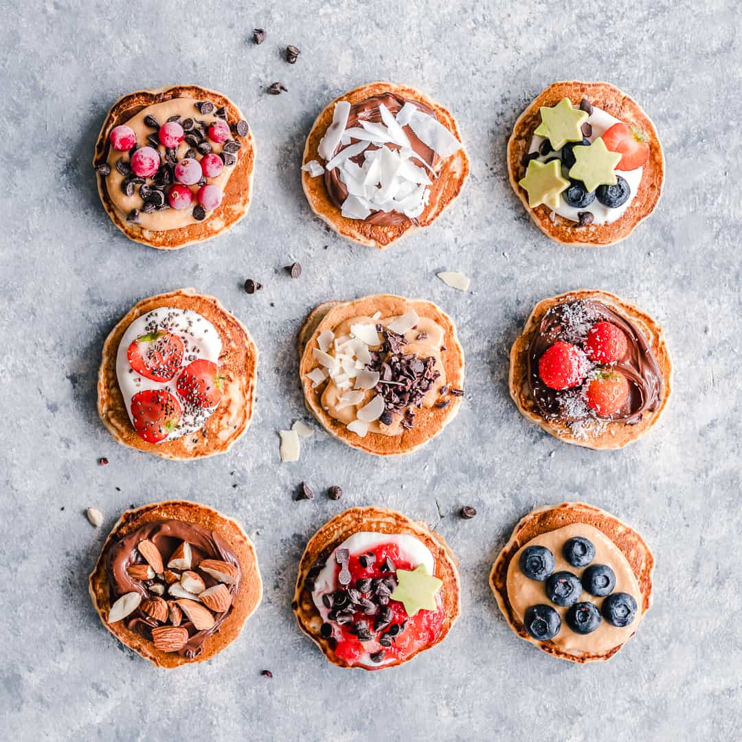 Top view of 9 fluffy pancakes with different toppings