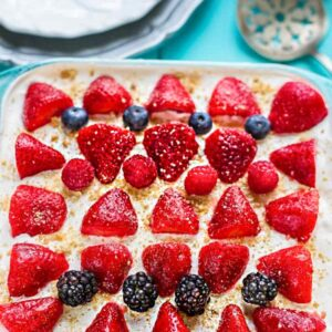 Top view of mixed berry icebox cake in a square pan on a blue background